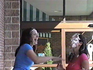 Two girls pie each other